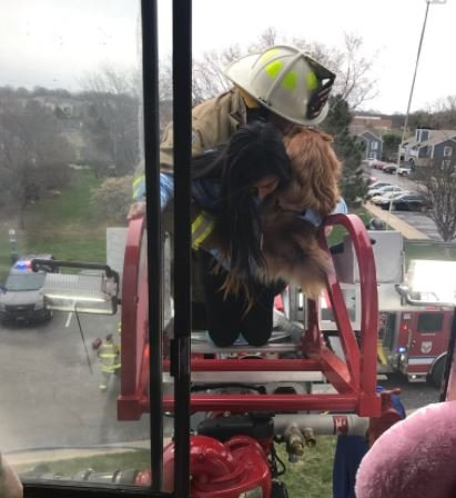 The Overland Park Fire Department helped several people escape a burning apartment building earlier today, including this young woman and her dog. (Submitted photo)