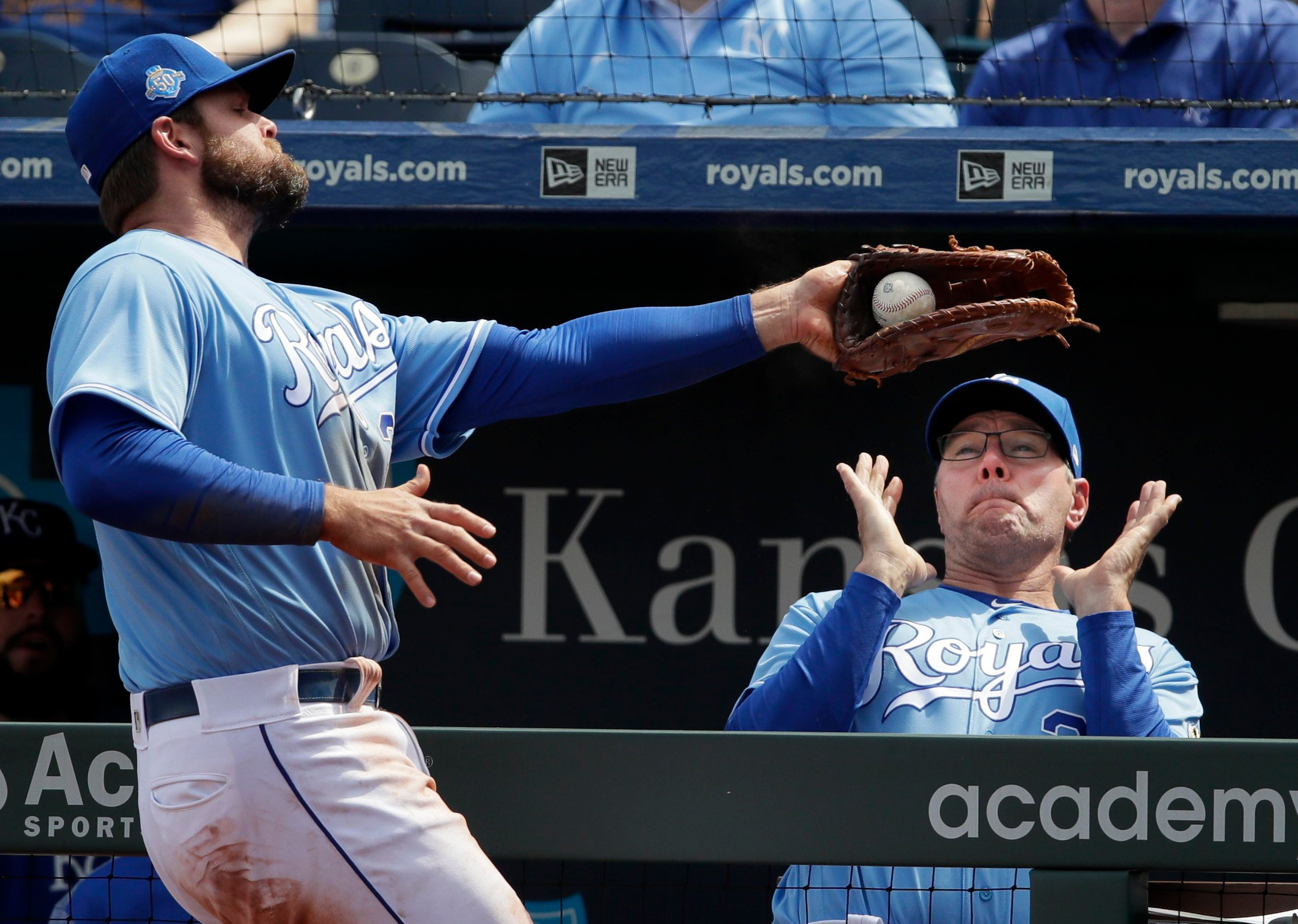 Royals first baseman Lucas Duda, left, catches a foul ball near the dugout hit by Seattle Mariners' Guillermo Heredia during the fourth inning in Kansas City. Kansas City Kansas City Royals pitching coach Cal Eldred, right, gets out of the way. (AP)