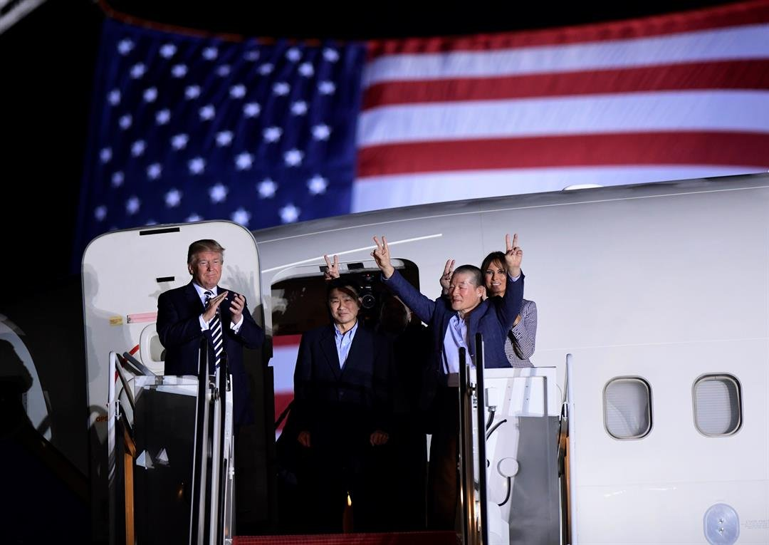 Under an American flag and dark night sky, US President Donald Trump personally welcomed home three American detainees Thursday morning after they were released from North Korea. (AP Photo)