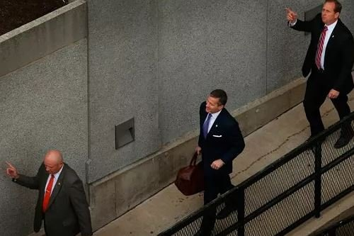 (David Carson/St. Louis Post-Dispatch via AP). In this May 10, 2018, photo, flanked by security guards, Missouri Gov. Eric Greitens, center, arrives at court for jury selection in his felony invasion of privacy trial, in St. Louis.