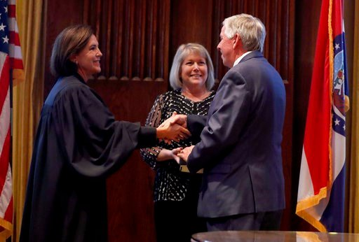 Missouri Lt. Gov. Mike Parson, right, shakes hands after being sworn in as the state's 57th governor by Judge Mary Rhodes Russell, left, as Parson's wife, Teresa, looks on following the resignation of Eric Greitens Friday, June 1. (AP Photo/Jeff Roberson)