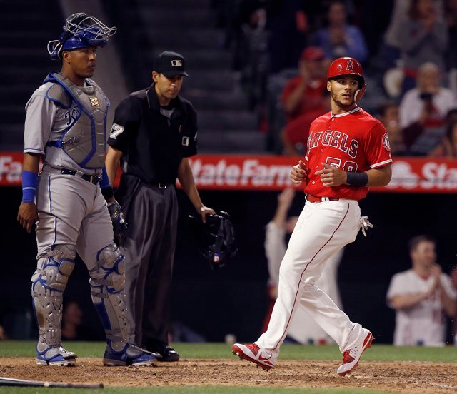 Los Angeles Angels' Michael Hermosillo, right, scores in front of Kansas City Royals catcher Salvador Perez on a single to by Justin Upton during the eighth inning of a baseball game in Anaheim, Calif., Monday, June 4, 2018. (AP Photo/Alex Gallardo)