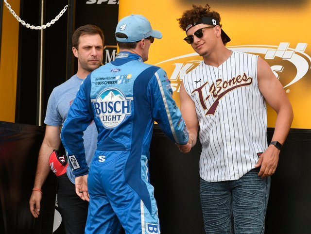 Brett Veach, left, general manager of the Kansas City Chiefs,and Chiefs quarterback Patrick Mahomes greet Kevin Harvick during driver introductions for the NASCAR Cup Series auto race at Kansas Speedway. (AP Photo/Ed Zurga)