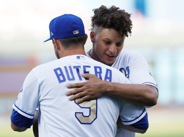 Kansas City Chiefs quarterback Patrick Mahomes, right, is hugged by Kansas City Royals catcher Drew Butera (9) after throwing out the ceremonial first pitch before a baseball game against the New York Yankees at in Kansas City. (AP Photo/Colin E. Braley)