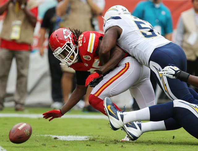 Kansas City Chiefs running back Jamaal Charles (25) fumbles as he is hit by San Diego Chargers inside linebacker Takeo Spikes (51) during the first half of an NFL football game at Arrowhead Stadium.  (AP Photo/Ed Zurga)