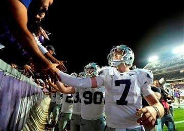 (AP Photo/LM Otero). Kansas State quarterback Collin Klein (7) and teammates celebrates with fans in the stands after the NCAA college football game against TCU, Saturday, Nov. 10, 2012, in Fort Worth, Texas.