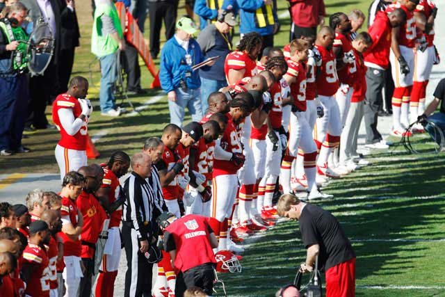 Kansas City Chiefs players stand for a moment of silence before the start of an NFL football game against the Carolina Panthers at Arrowhead Stadium in Kansas City, Mo., Sunday, Dec. 2, 2012. (AP Photo/Orlin Wagner)