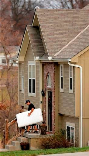 (AP Photo/Charlie Riedel). An unidentified man carries items out of a Kansas City home shared by Kansas City Chiefs linebacker Jovan Belcher and his 22-year-old girlfriend Kasandra Perkins, Monday, Dec. 3, 2012.