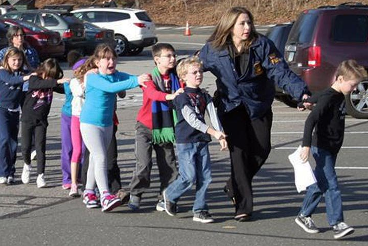 © : In this photo provided by the Newtown Bee, Connecticut State Police lead children from the Sandy Hook Elementary School in Newtown, Conn., following a reported shooting there Friday, Dec. 14, 2012. (AP Photo/Newtown Bee, Shannon Hicks)