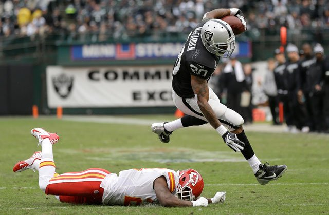 Oakland Raiders running back Darren McFadden (20) leaps past Kansas City Chiefs cornerback Javier Arenas (21) during the first quarter of an NFL football game in Oakland, Calif., Sunday, Dec. 16, 2012. (AP Photo/Marcio Jose Sanchez)