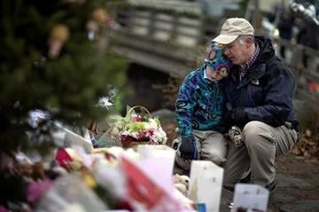 (AP Photo/David Goldman). David Freedman, right, kneels with his son Zachary, 9, both of Newtown, Conn., as they visit a sidewalk memorial for the Sandy Hook Elementary School shooting victims, Sunday, Dec. 16, 2012, in Newtown, Conn.