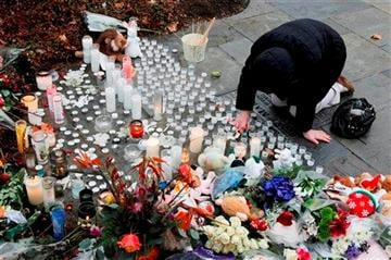 (AP Photo/Julio Cortez) A woman pays respects at a memorial outside of St. Rose of Lima Roman Catholic Church, Sunday, Dec. 16, 2012, in Newtown, Conn.