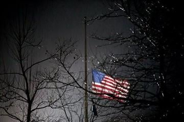(AP Photo/David Goldman) A U.S. flag flies at half staff outside the Newtown High School before President Barack Obama is scheduled to attend a memorial for the victims of the Sandy Hook Elementary School shooting, Sunday, Dec. 16, 2012, in Newtown, Conn.