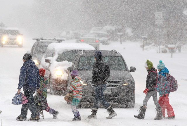Elementary school students, some escorted by parents, cross a snowy street en route to school as a blizzard dropped snow over Boulder, CO, Wednesday Dec. 19, 2012. (AP Photo/Brennan Linsley)