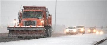 A snow plow spreads salt and sand Wednesday Dec. 19, 2012 in Omaha, Neb. (AP Photo/The World-Herald, Jimmie Burnett)
