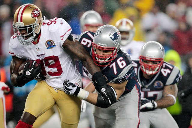 San Francisco 49ers outside linebacker Aldon Smith (99) runs after intercepting a pass as New England Patriots tackle Sebastian Vollmer (76) and tight end Michael Hoomanawanui (47) pursue in Foxborough, Mass., Sunday, Dec. 16, 2012.(AP Photo/Steven Senne)