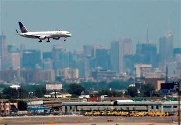 (AP Photo/Julio Cortez, File). FILE - In this July 10, 2012 file photo, a United plane prepares to land at Newark Liberty International Airport in Newark, N.J., with the New York City skyline in the background.