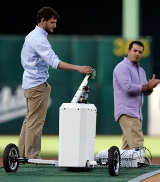 A telerobotic pitching machine is loaded with a baseball to throw out the ceremonial first pitch in Oakland, Calif.  Nick LeGrande made the toss from his hometown of Kansas City by using the machine. (AP Photo/Ben Margot)
