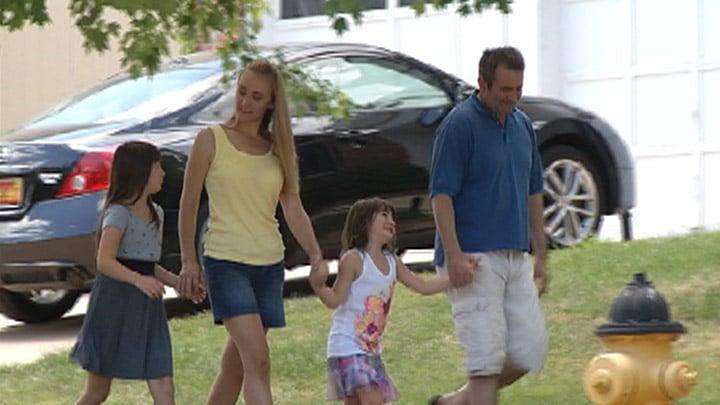 Heather MacKenzie walks in her neighborhood with her family
