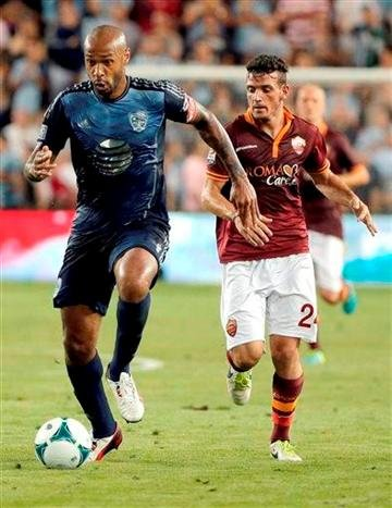 (AP Photo/Charlie Riedel). MLS All-Stars forward Thierry Henry, left, dribbles the ball as AS Roma midfielder Alessandro Florenzi (24) chases during the first half of the MLS All-Star soccer game Wednesday, July 31, 2013, in Kansas City, Kan.