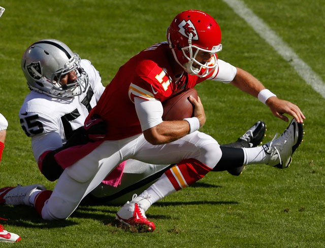 Kansas City Chiefs quarterback Alex Smith (11) is sacked by Oakland Raiders outside linebacker Sio Moore (55) during the first half of an NFL football game at Arrowhead Stadium in Kansas City, Mo., Sunday, Oct. 13, 2013. (AP Photo/Orlin Wagner)