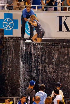 A fan us helped from the outfield fountains during a baseball game between the Minnesota Twins and the Kansas City Royals at Kauffman Stadium in Kansas City, Mo., Monday, Aug. 5, 2013. (AP Photo/Orlin Wagner)