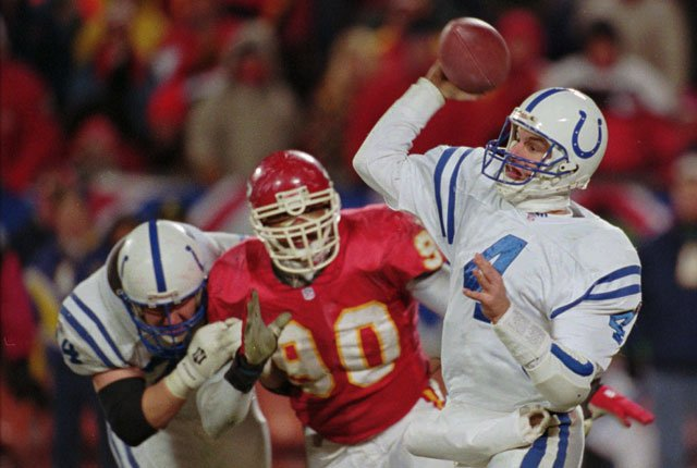 This Jan. 7, 1996 file photo shows Indianapolis Colts quarterback Jim Harbaugh (4) trying to get off a pass under pressure from Kansas City Chiefs defender Neil Smith (90). (AP Photo/Mark Duncan,File)