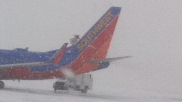 This photo (taken about 11 a.m. Tuesday) show crews working to de-ice a plane at KCI.
