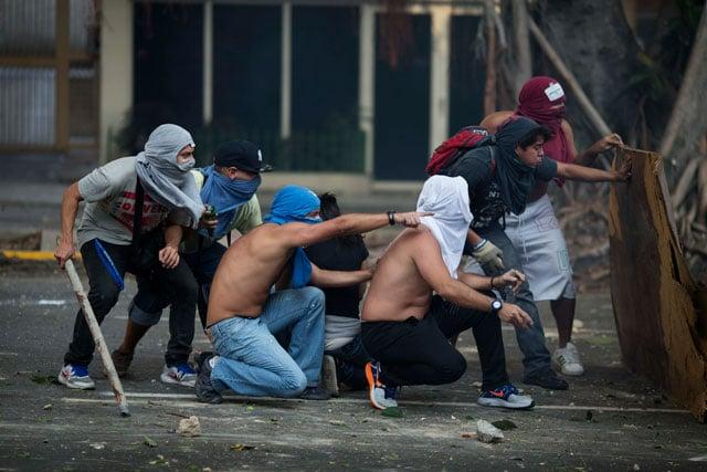 Anti-government protesters take cover during clashes with riot police in Caracas, Venezuela, Saturday, Feb. 22, 2014. (AP Photo/Rodrigo Abd)