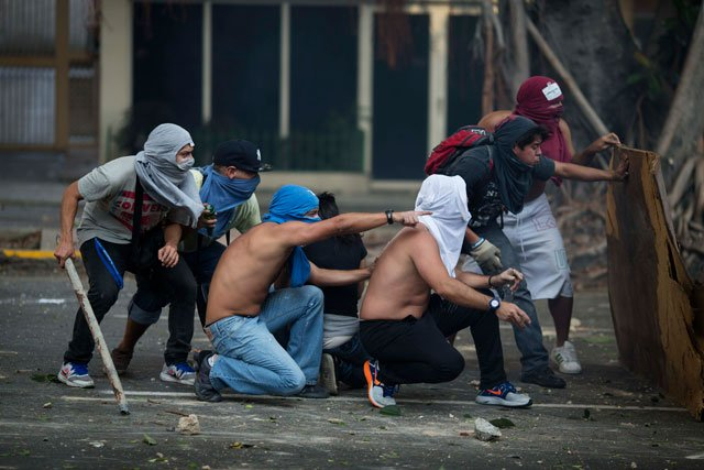Anti-government protesters take cover during clashes with riot police in Caracas, Venezuela, Saturday, Feb. 22, 2014. (AP Photo/Rodrigo Abd)