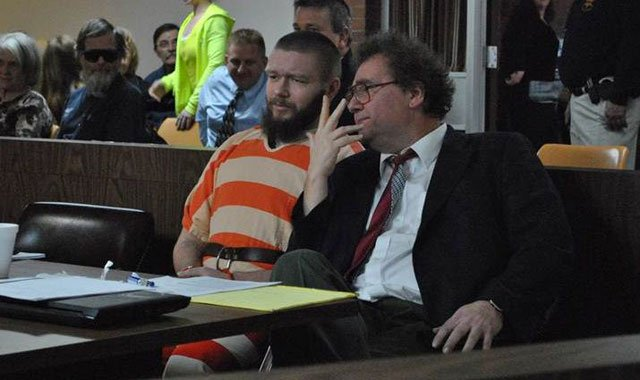 Kyle T. Flack, 28, Ottawa, who is charged in connection with the killing of three adults and an 18-month-old girl in spring 2013, talks Monday morning with his court-appointed lawyer, Ronald Evans, in Franklin County District Court.