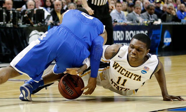 Kentucky guard Andrew Harrison (5) and Wichita State forward Cleanthony Early (11) go after a loose ball during the first half of a third-round game of the NCAA college basketball tournament Sunday, March 23, 2014, in St. Louis. (AP Photo/Charlie Riedel)