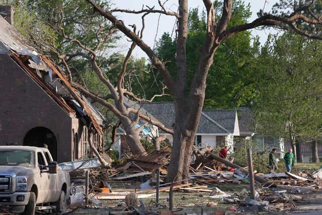Residents view damage from a Sunday night tornado in Baxter Springs, KS, Monday, April 28, 2014. The tornado left a trail of shattered homes, twisted metal and hanging power lines. (AP Photo/Orlin Wagner)