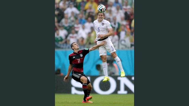 United States' Matt Besler goes up to head the ball over Germany's Miroslav Klose during the group G World Cup soccer match between the United States and Germany (AP Photo/Julio Cortez)