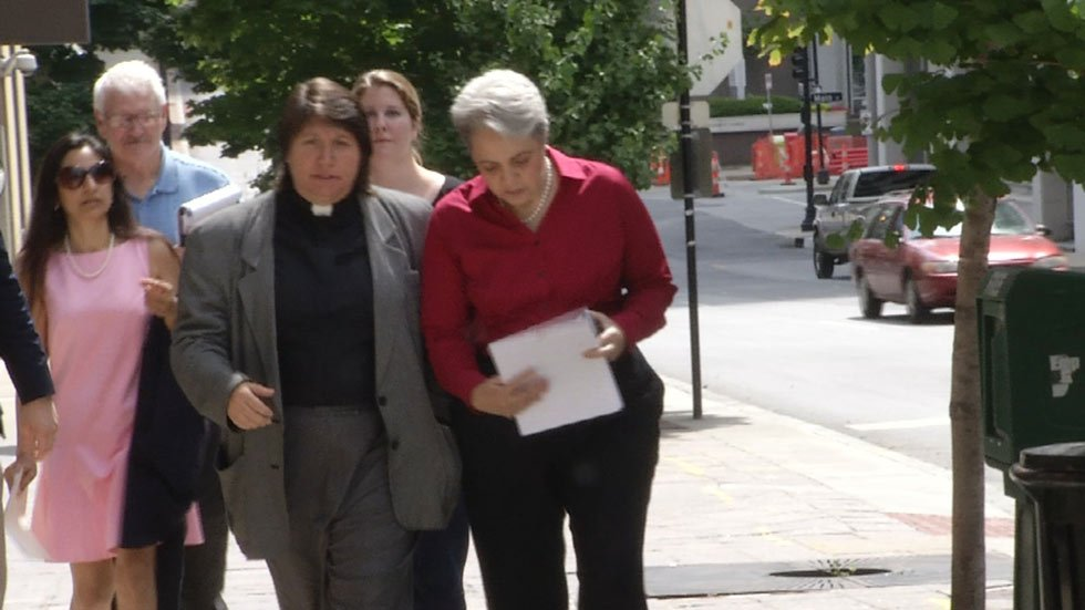 Reverend Donna Simon and Colleen Simon walk with lawyers and friends.