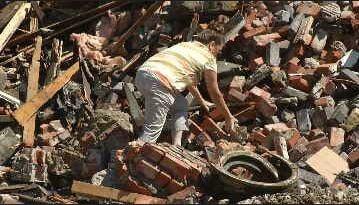 Shiela Alcorn collects some bricks from the Rios De Agua Viva Church debris.