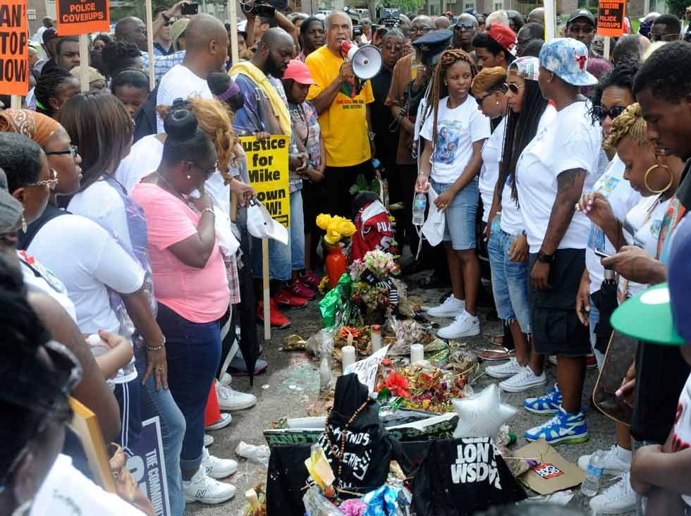 Demonstrators join family members of Michael Brown during a moment of silence at the site of the shooting in Ferguson, Mo. on Saturday, Aug. 30. (AP Photo/Bill Boyce)