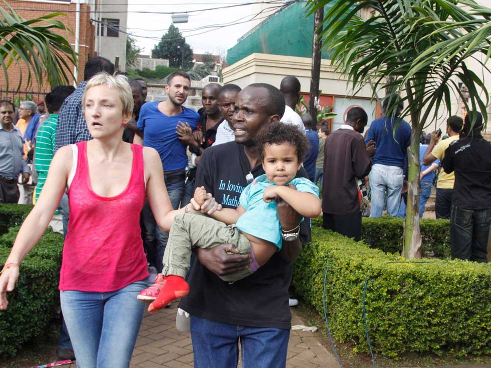 The mother and a security guard help a child outside the Westgate Mall in Nairobi, Kenya after terrorists opened fire (AP)