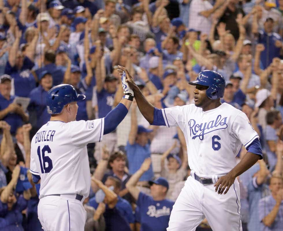 Kansas City Royals' Lorenzo Cain (6) and Billy Butler (16) celebrate after Cain scored on a single by Eric Hosmer during the third inning of the AL wild-card playoff baseball game against the Oakland Athletics Tuesday. (AP Photo/Charlie Riedel)