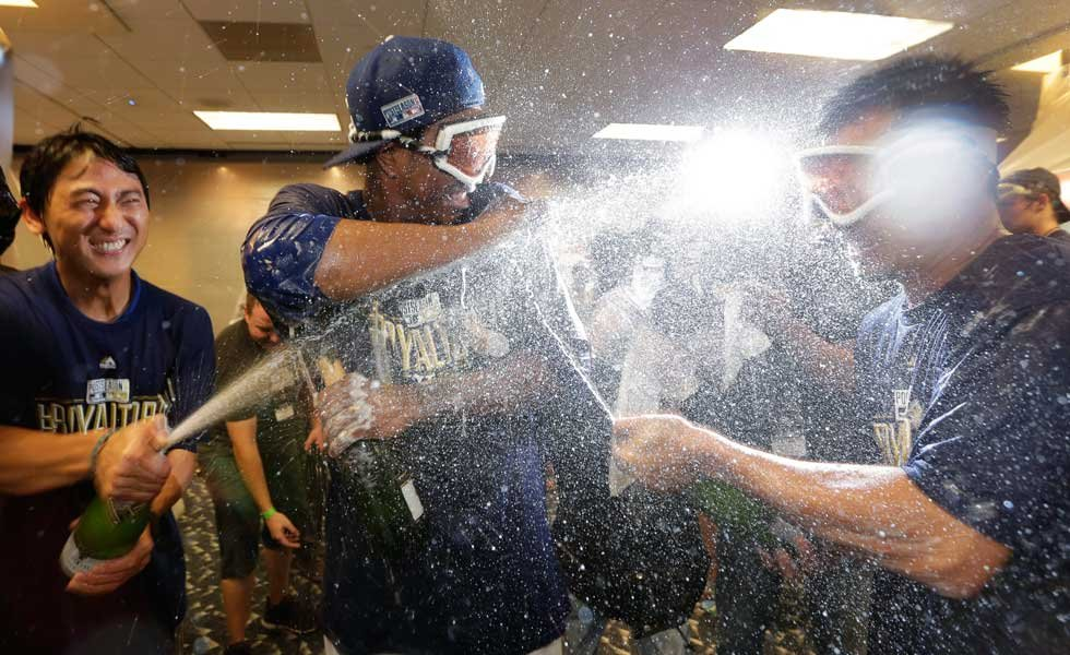 Royals interpreter Kosuke Inaji, left, pitcher Yordano Ventura, center, & right fielder Norichika Aoki, right, celebrate in the clubhouse after the Royals' 9-8 win in 12 innings in the AL wild-card playoff  game. (AP Photo/Charlie Riedel)