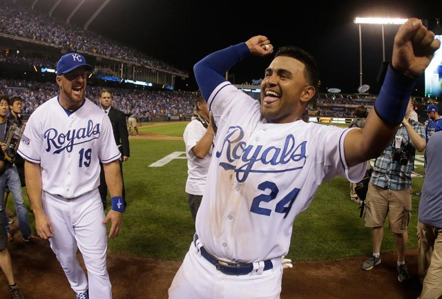 Kansas City Royals' Christian Colon (24) and Erik Kratz celebrate after their 9-8 win in the AL wild-card playoff baseball game against the Oakland Athletics Wednesday, Oct. 1, 2014, in Kansas City, Mo. (AP Photo/Charlie Riedel)