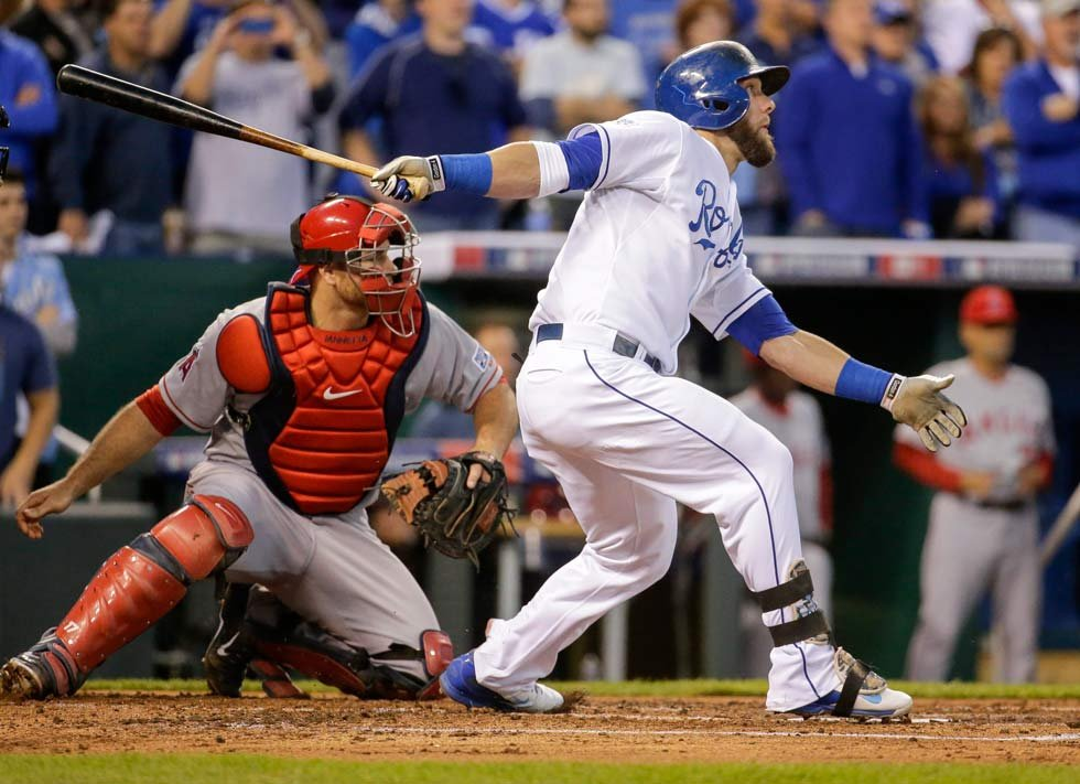 Kansas City Royals' Alex Gordon, right, follows his three-RBI double with Los Angeles Angels catcher Chris Iannetta, left, during the first inning of Game 3 of baseball's AL Division Series in Kansas City, Mo., Sunday, Oct. 5. (AP Photo/Charlie Ried)