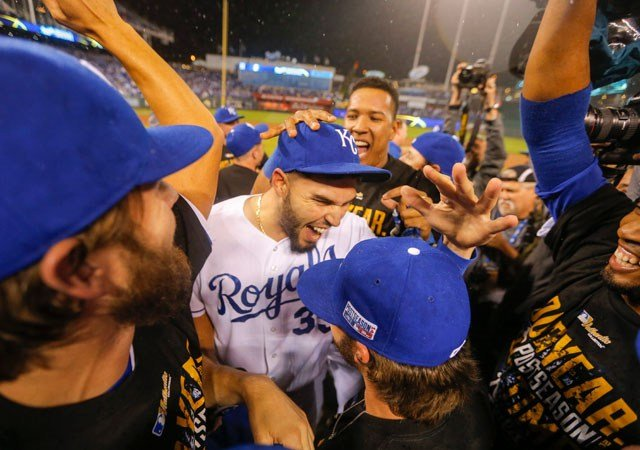 Kansas City Royals first baseman Eric Hosmer, center and catcher Salvador Perez, rear right, and teammates celebrate following Game 3 of baseball's AL Division Series in Kansas City, Mo., Sunday, Oct. 5, 2014. (AP Photo/Travis Heying)