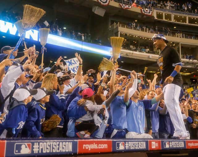 Kansas City Royals catcher Salvador Perez (13) celebrates with fans holding brooms following Game 3 of baseball's AL Division Series in Kansas City, Mo., Sunday, Oct. 5, 2014. (AP Photo/Travis Heying)
