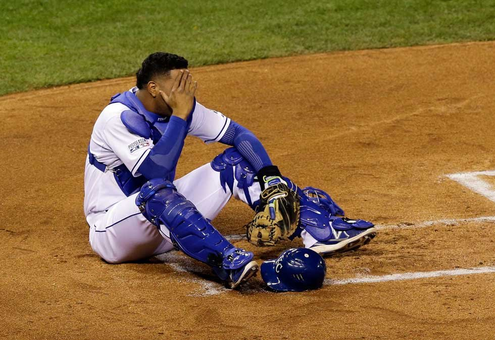 Kansas City Royals catcher Salvador Perez holds his head after being hit by a bat during the first inning of Game 3 of the American League baseball championship series against the Baltimore Orioles Tuesday, Oct. 14 in Kansas City (AP Photo/Chris O'Meara)