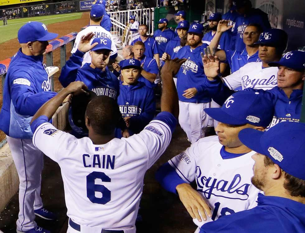 Kansas City Royals' Lorenzo Cain is congratulated after scoring a run during the sixth inning of Game 2 of baseball's World Series against the San Francisco Giants Wednesday, Oct. 22, 2014, in Kansas City, Mo. (AP Photo/David J. Phillip)