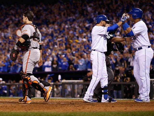 San Francisco Giants Buster Posey walks past as Kansas City Royals Salvador Perez, right, congratulates Omar Infante after Infante's two-run home run during the sixth inning Wednesday, Oct. 22, 2014, in Kansas City, Mo. (AP Photo/Matt Slocum)