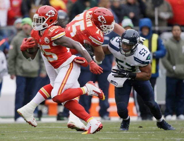 Kansas City Chiefs running back Jamaal Charles (25) carries the ball as Chiefs guard Mike McGlynn (75) blocks Seattle Seahawks outside linebacker Malcolm Smith (53) in the first half of an NFL football game in Kansas City. (AP Photo/Charlie Neibergall)