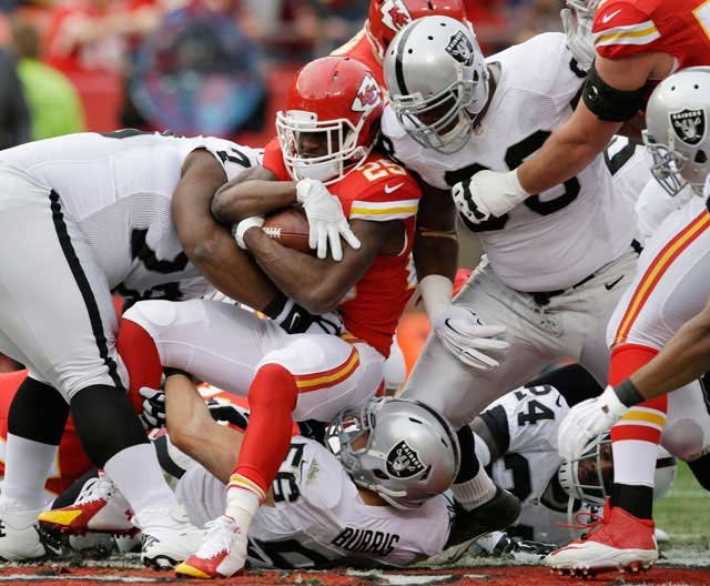 Kansas City Chiefs running back Jamaal Charles (25) is tackled by Oakland Raiders middle linebacker Miles Burris (56) and Oakland Raiders defensive end C.J. Wilson, right, during the first half Sunday in Kansas City. (AP Photo/Orlin Wagner)