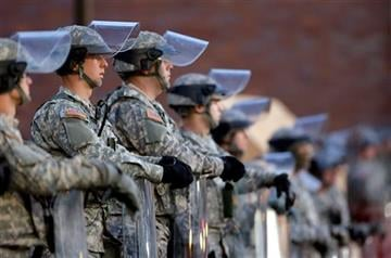 National Guard troops stand in front of the Ferguson, Mo., Police Department a day after a grand jury's decision in the fatal shooting of Michael Brown. (AP Photo/Charlie Riedel, File)
